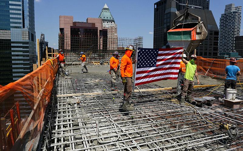 Construction Workers Hoisting U.S flag